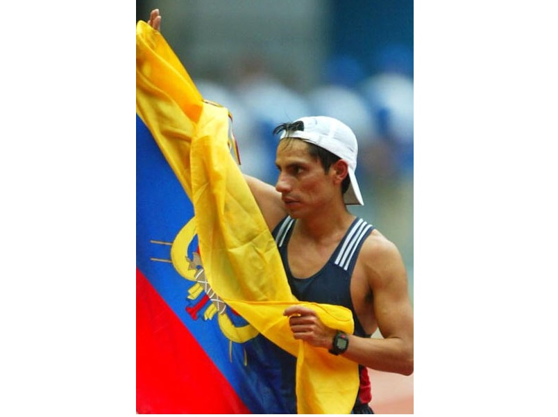 PARIS - AUGUST 23:  Jefferson Perez of Ecuador draped in the a flag celebrates his win in the men's walk at the 9th IAAF World Athletics Championships August 23, 2003 in Paris.   (Photo by /Getty Images)